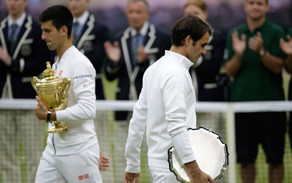 Novak Djokovic of Serbia, left, and Roger Federer of Switzerland hold their trophies after Djokovic won the men's singles final at the All England Lawn Tennis Championships in Wimbledon, London.