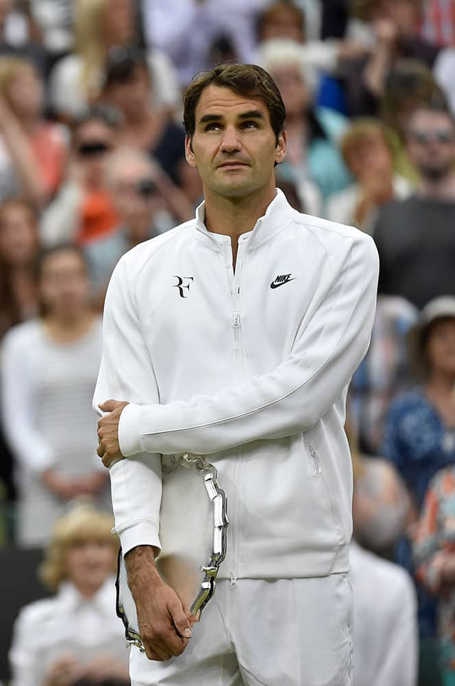 Roger Federer of Switzerland holds the runner up trophy up after being defeated by Novak Djokovic of Serbia in the men's singles final at the All England Lawn Tennis Championships in Wimbledon, London.