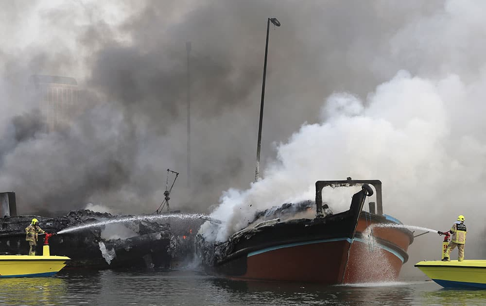 Smokes rise from two trading dhows as firefighters spray water to distinguish the fire at the Dubai creek, in Dubai, United Arab Emirates.