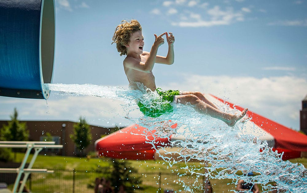 Bodie Emanoil, 10, exits the water slide at Clive Aquatic Center as temperatures rise in Clive, Iowa.