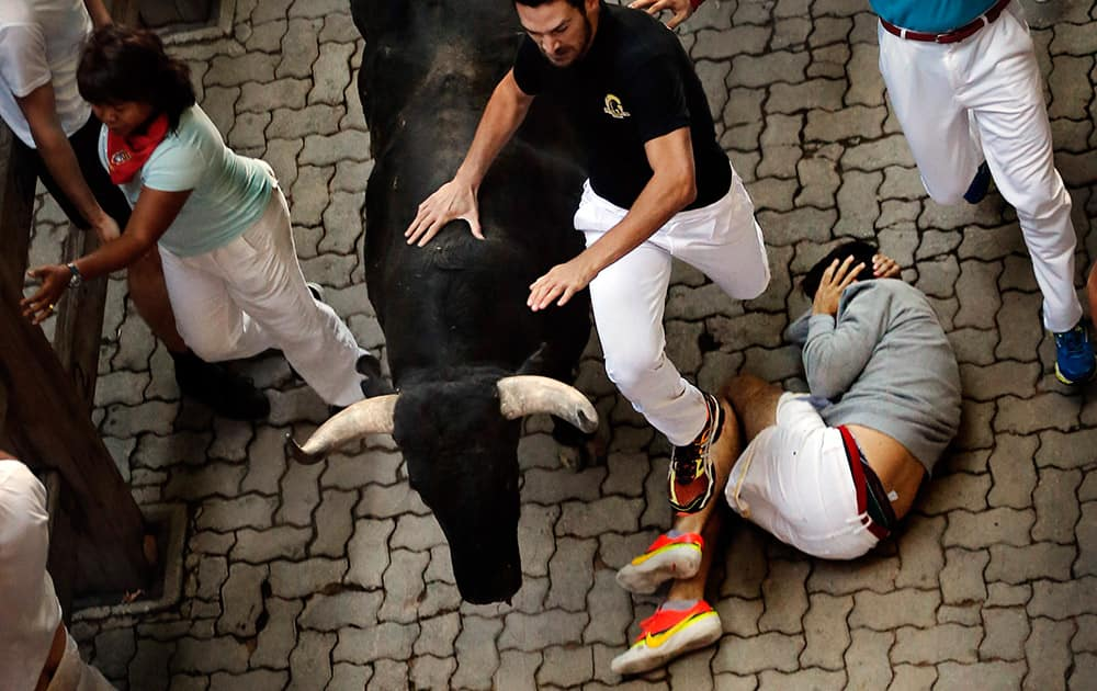 A fallen man covers his head while other revelers run alongside Garcigrande ranch fighting bulls during the daily morning running of the bulls of the San Fermin festival in Pamplona, Spain.