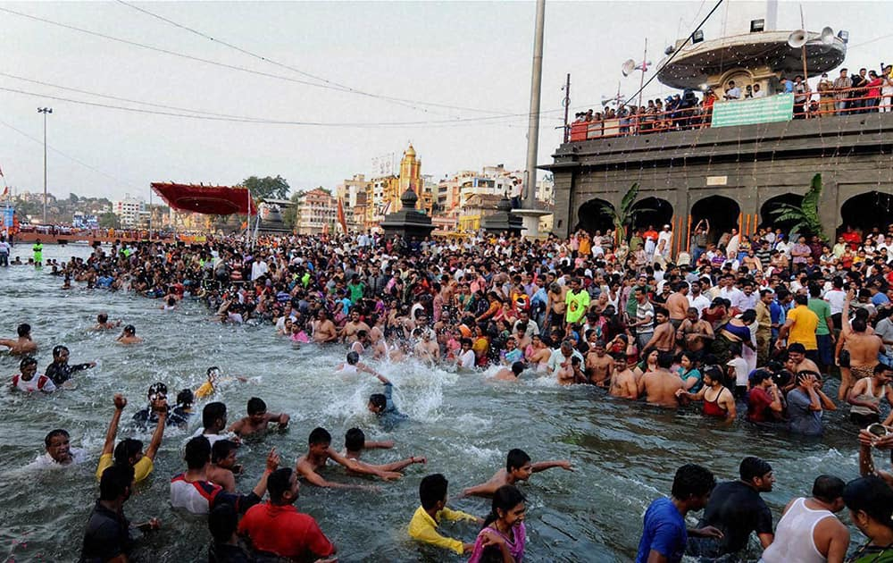 Devotees taking holy bath in Godavari River during the Simhastha Kumbha Mela in Nashik.