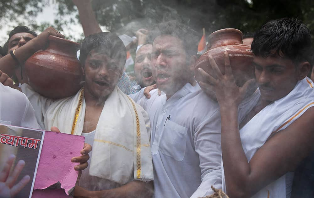 Activists of India's opposition Congress party's youth wing enact a mock Hindu funeral during a protest against a multimillion-dollar college admission and government job recruitment scandal in New Delhi, India.