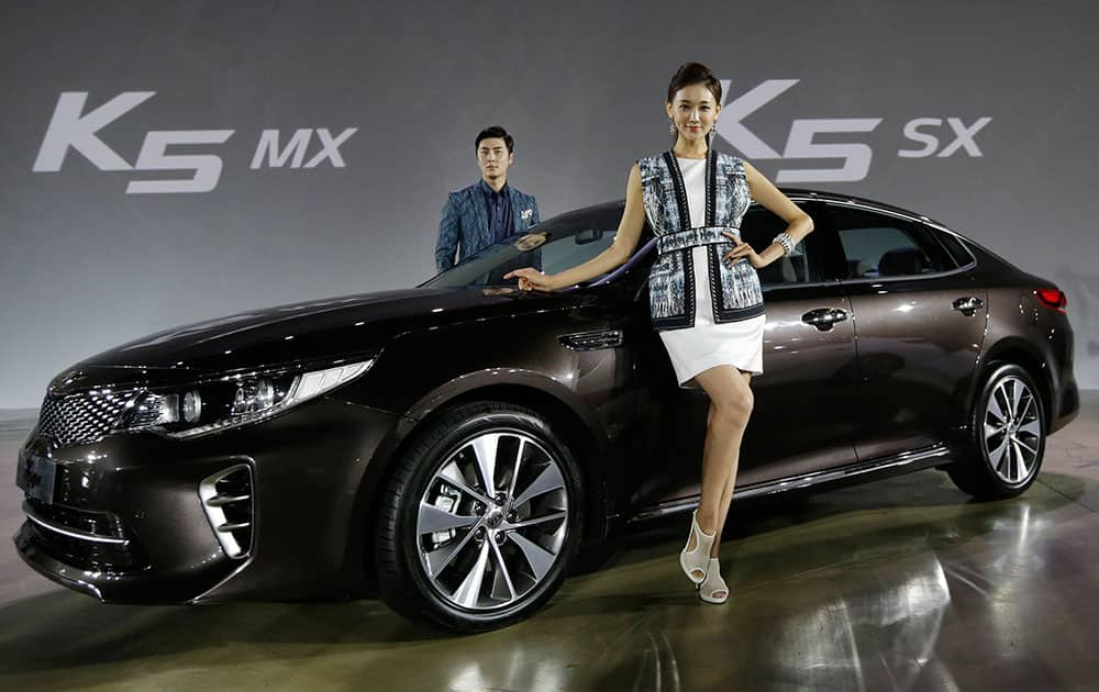 Models pose with Kia Motors' newly-launched K5 sedan during an unveiling ceremony in Seoul, South Korea.