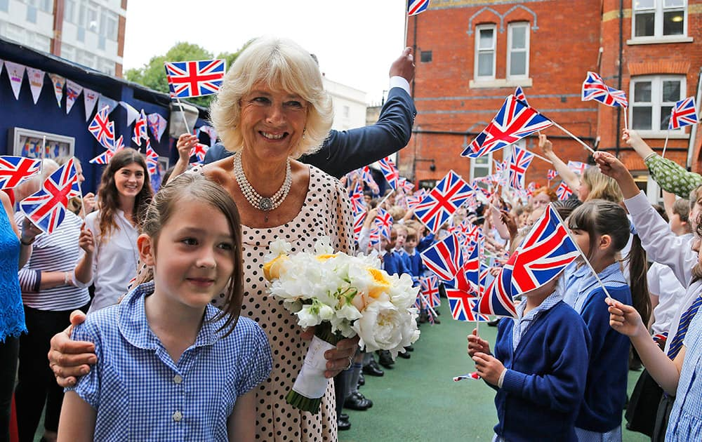 Well wishers wave Union Flags as the Duchess of Cornwall visits St. Peter's Eaton Square Church of England Primary School in London.