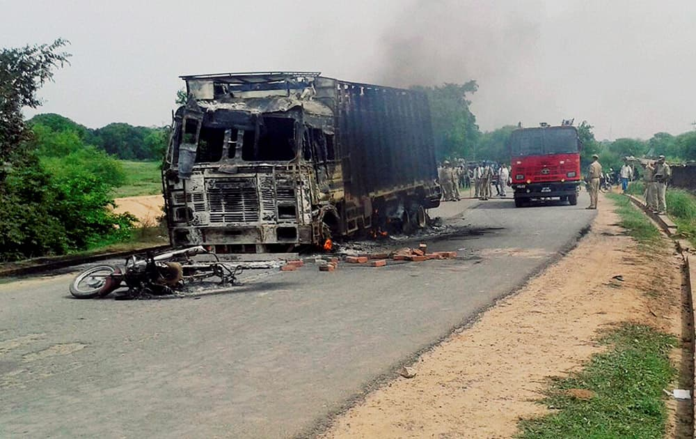 Police men standing near the trucks that were torched by angry villagers after an accident at Karchhana near Allahabad.
