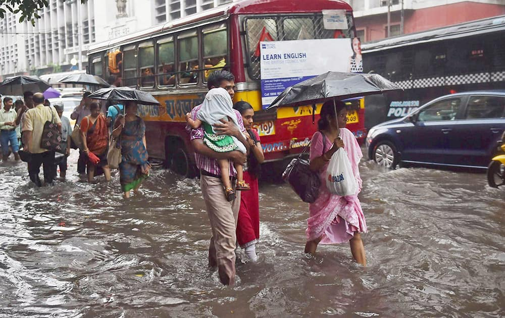People wade through a waterlogged road during a heavy downpour in Kolkata.