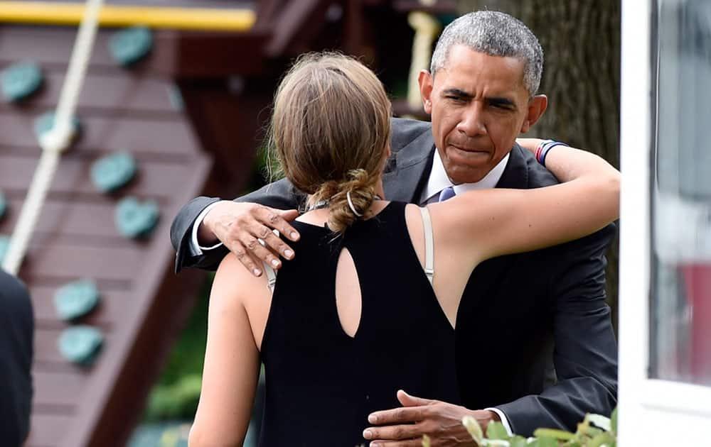 President Barack Obama stops to hug Finnegan Biden, granddaughter of Vice President Joe Biden, on the South Lawn of the White House in Washington.