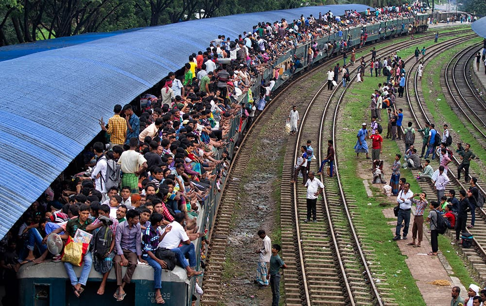 Bangladeshi passengers sit on the roof of a train, as they head to their homes to celebrate Eid al-Fitr in Dhaka, Bangladesh.