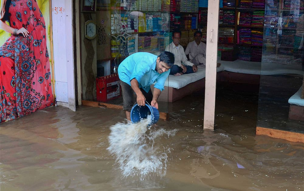 A shopkeeper removes water from his waterlogged shop after heavy rains in Varanasi.