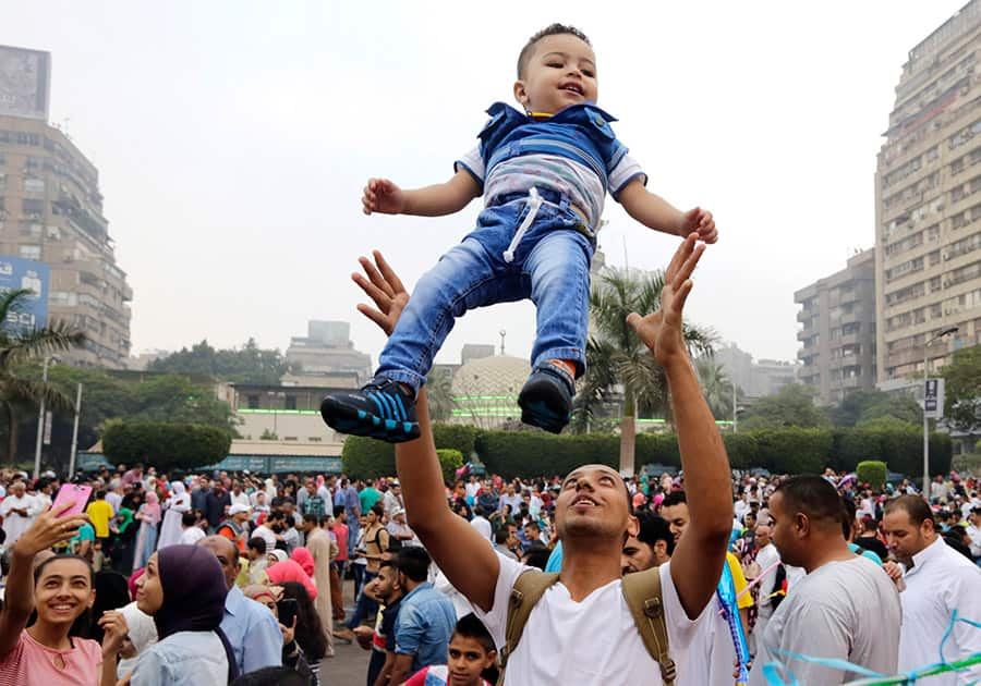 An Egyptian man tosses his son up in the air as people celebrate Eid al-Fitr feast, marking the end of the Muslim fasting month of Ramadan in Cairo, Egypt.