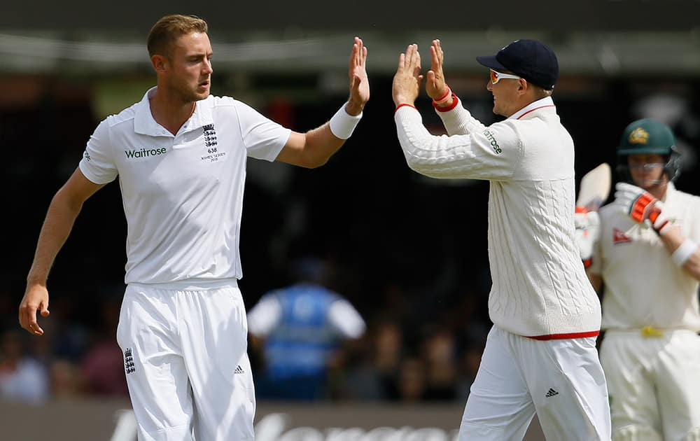 England's Stuart Broad and Joe Root celebrate taking the wicket of Australia's Chris Rogers on the second day of the second Ashes Test match between England and Australia, at Lord's cricket ground in London.