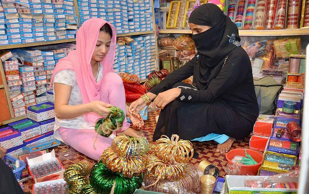 A Muslim woman purchasing bangles at a shop ahead of Eid-ul-Fitr festival in Mirzapur.