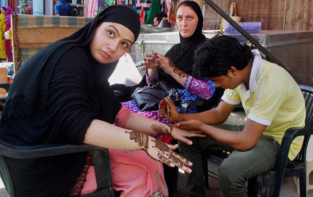 A Kashmiri girl getting her hand designed with Mehndi ahead of Eid-ul-fitr festival at Lal Chowk in Srinagar.