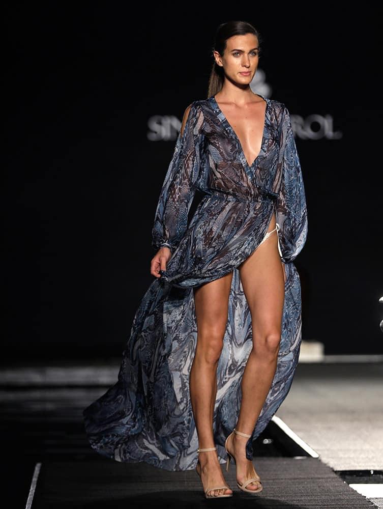 A model walks down the runway during the Sinesia Karol swimwear show as part of Funkshion Fashion Week Swim in Miami Beach, Fla.