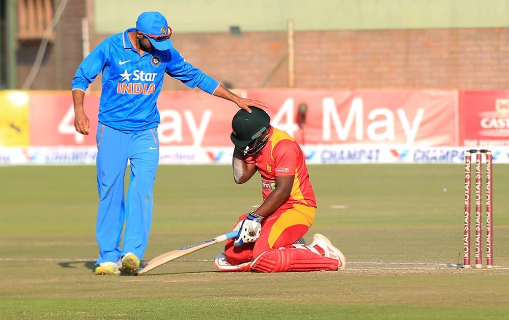 Ajinkya Rahane touches Zimbabwean batsman Prosper Utseya on the helmet after he fell to the ground in the Twenty20 cricket match against Zimbabwe in Harare, Zimbabwe.