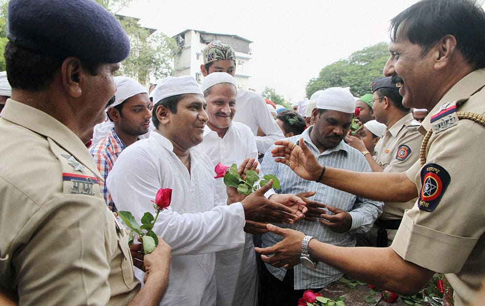 Police personnel offer roses to Muslims on the occasion of Eid-ul-Fitr festival in Thane, Mumbai.