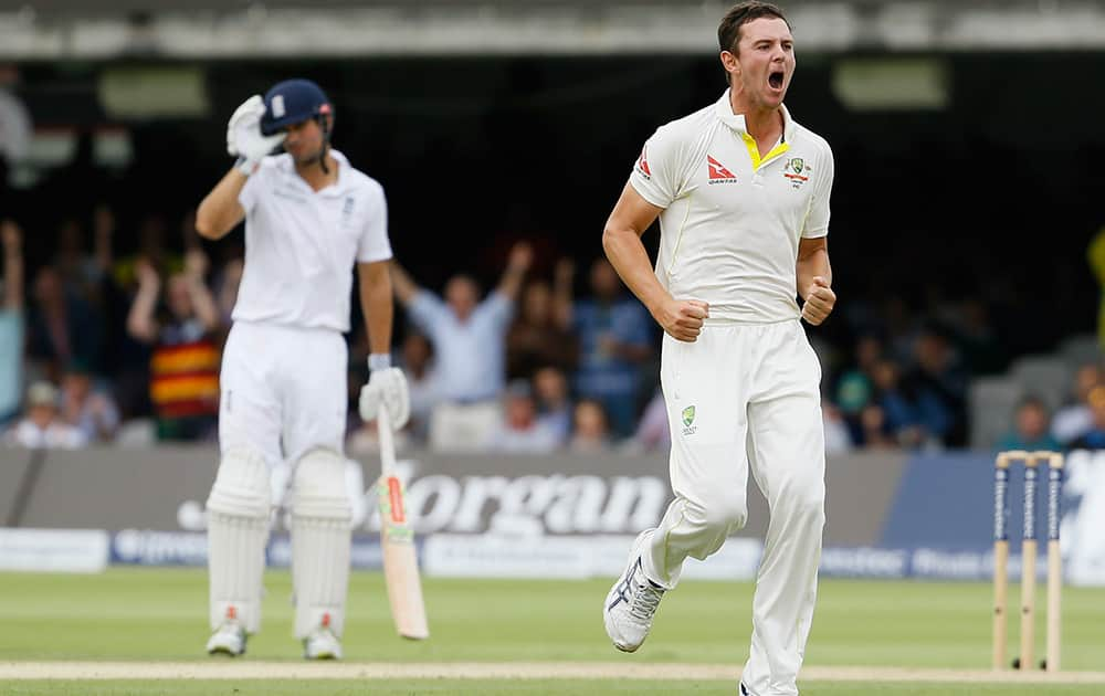 Australia's Josh Hazlewood runs past Alastair Cook to celebrate taking the wicket of England's Ian Bell on the second day of the second Ashes Test match between England and Australia, at Lord's cricket ground in London.