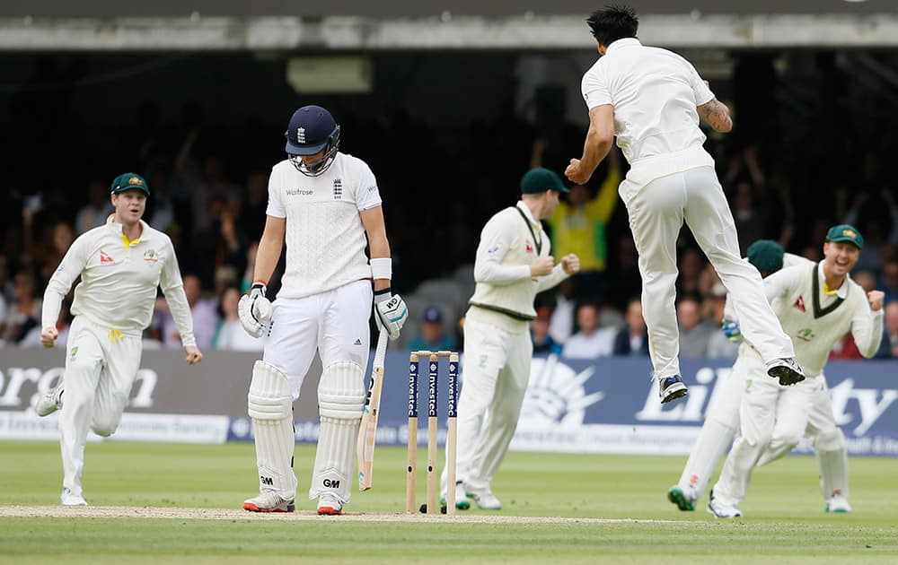 England's Joe Root looks down as Australia's Mitchell Johnson jumps to celebrate taking his wicket on the second day of the second Ashes Test match between England and Australia, at Lord's cricket ground in London.