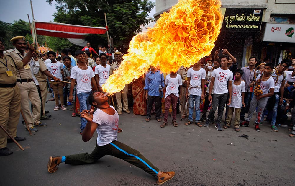 A man performs fire stunt during the annual Rath Yatra or Chariot procession of Lord Jagannath in Ahmadabad.
