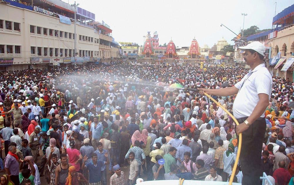 A volunteer sprays water on devotees during Nabakalebara Rathyatra in Puri.