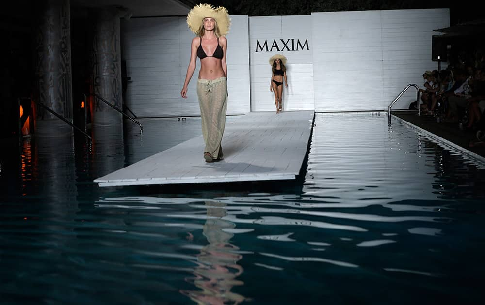 A model walks down the runway during the Maxim Swimwear collection launch as part of Funkshion Fashion Week Swim in Miami Beach, Fla.