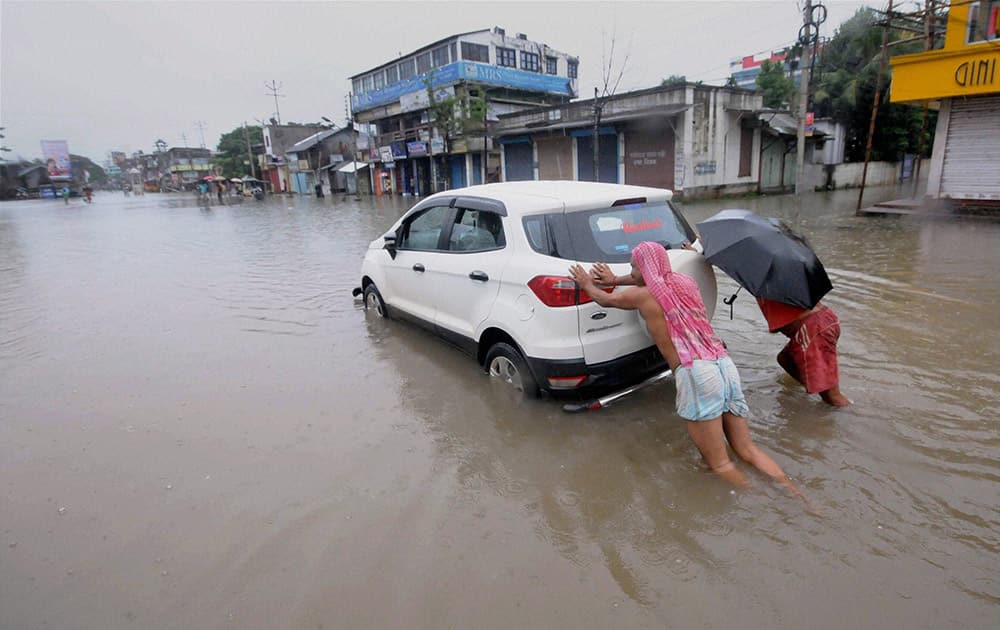 A car being pushed through a flooded street after rains in Agartala.