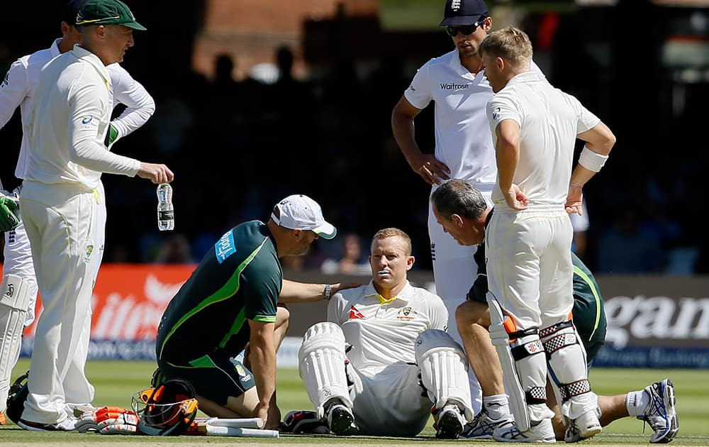 Australia's batsman Chris Rogers sits on the ground as he gets ill, and retires not out on the fourth day of the second Ashes Test match between England and Australia, at Lord's cricket ground in London.