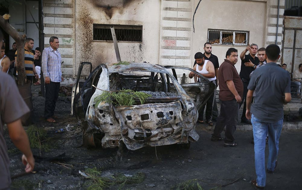 Palestinians stand around a vehicle destroyed in blast in Gaza City. At least four explosions rocked Gaza City early Sunday, targeting vehicles belonging to officials from Islamic factions, including the territorys Hamas rulers. There was no claim of responsibility, but speculation immediately centered on supporters of the Islamic State group, who have been battling with Hamas and other Islamic groups in the small coastal strip.