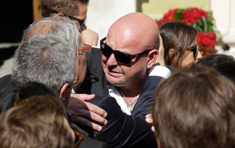 Philippe Bianchi, the father of French Formula One driver Jules Bianchi, is comforted by a relative prior to the funeral of his son at Sainte Reparate Cathedral in Nice, French Riviera.