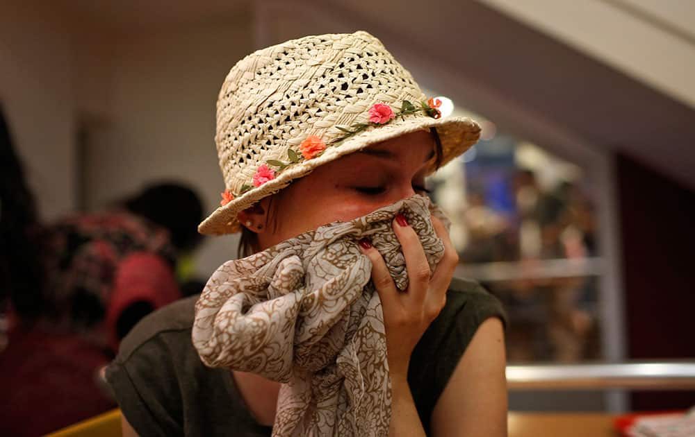 A protester tries to protect herself from the effects of tear gas fired by police in Istanbul.