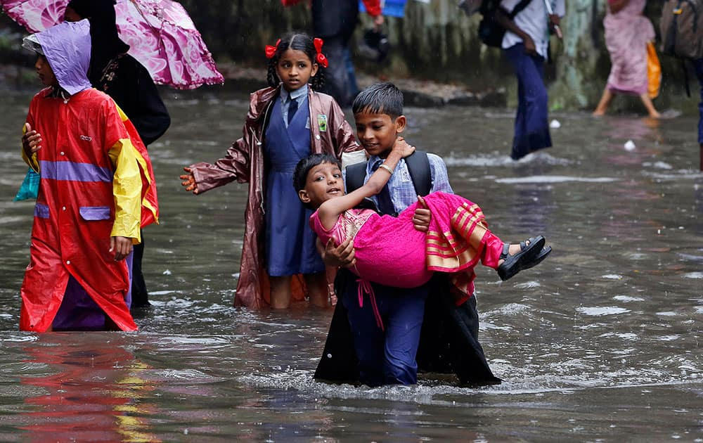 A boy carries his sister and wades through a waterlogged street on his way to school as it rains in Mumbai, Maharashtra state, India.
