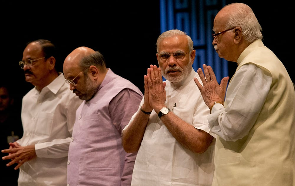 Prime Minister Narendra Modi and senior Bharatiya Janata Party (BJP) leader L.K.Advani, greet each other as BJP president Amit Shah and Venkaiah Naidu, left stand beside during the BJP parliamentary party meeting before the start of second day of the monsoon session of parliament, in New Delhi.