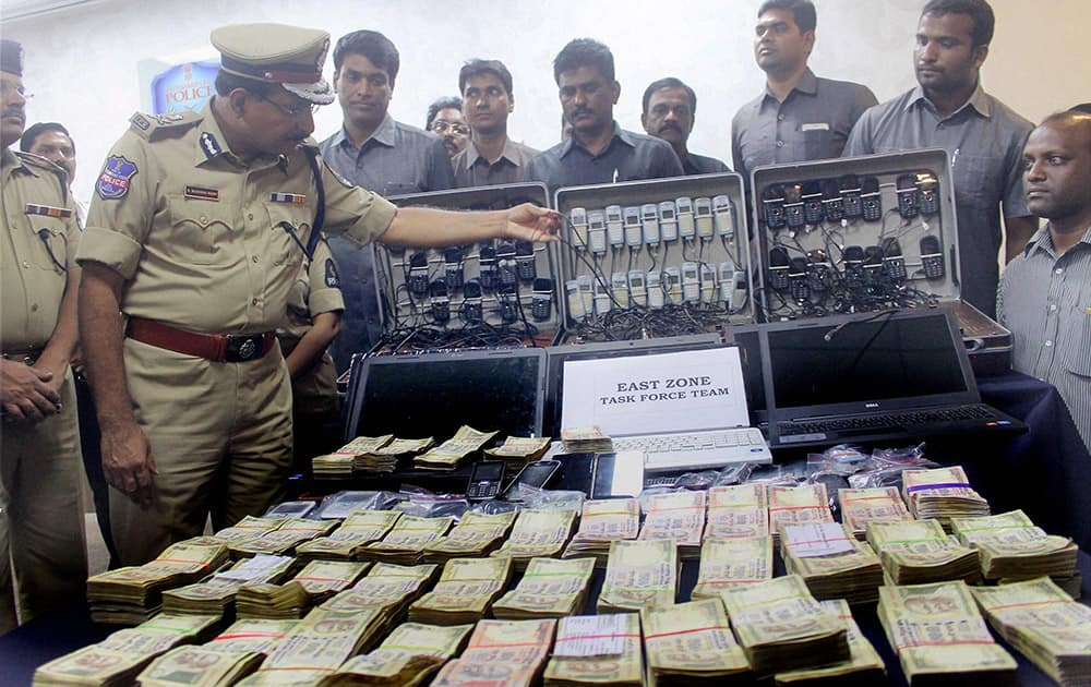 Police showing cash and mobiles recovered after bust of cricket betting racket in Hyderabad.