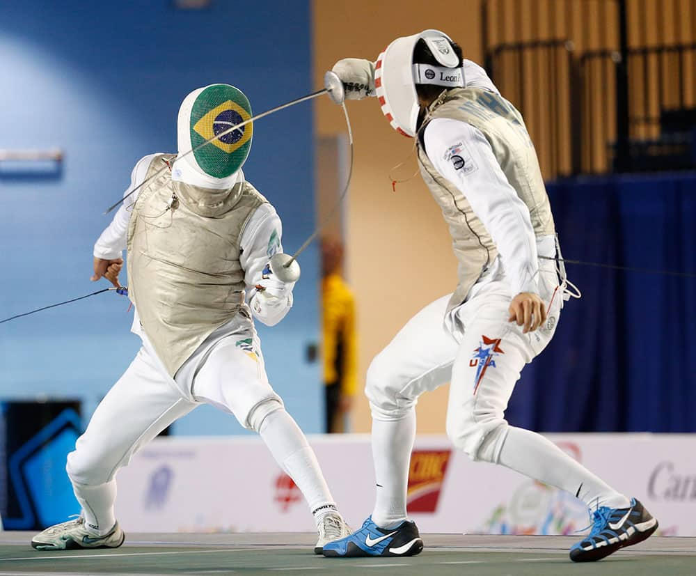 United States' Gerek Meinhardt, left, competes against Brazil's Ghislain Perrier in a men's foil individual semifinal fencing match at the Pan Am Games, in Toronto.