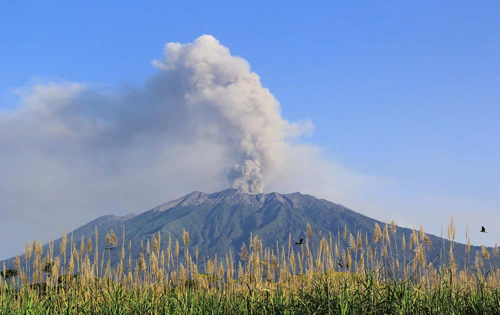Mount Raung spews volcanic material into the air as seen from Songgon, East Java, Indonesia.