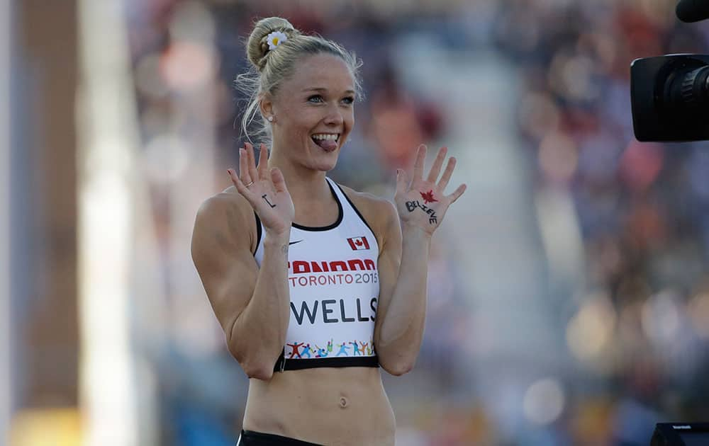 Canada's Sarah Wells gestures to a camera after the final of the women's 400 meter hurdles at the Pan Am Games in Toronto.