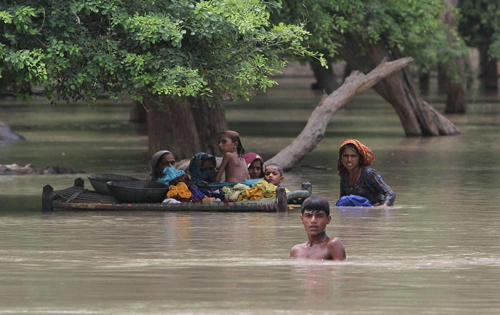 Pakistani villagers wade through floodwaters in Rajanpur, Pakistan.