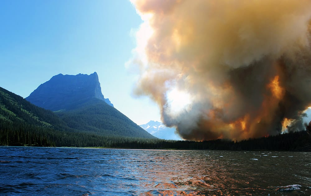 smoke from the Reynolds Creek wildfire rises above the landscape at St. Mary Lake in Glacier National Park, Mont.