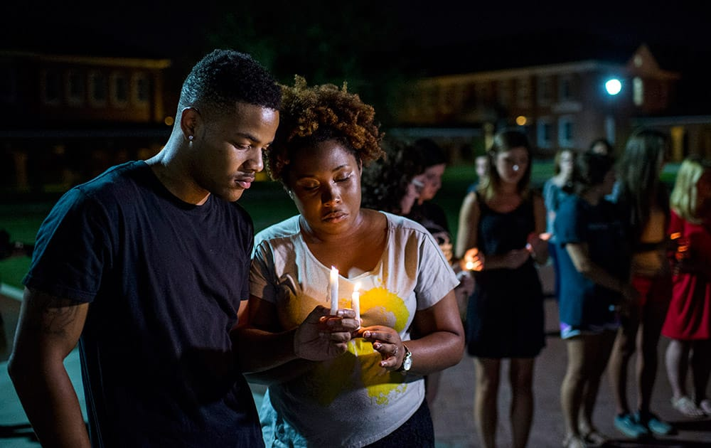 Sheldon Gilton, a business student, and Brea Butler, a psychology student, pray during a candlelight vigil for The Grand 16 theater shooting victims at the University of Louisiana at Lafayette in Lafayette, La. John Russell Houser stood up about 20 minutes into Thursday night's showing of 'Trainwreck' and fired on the audience with a semi-automatic handgun.