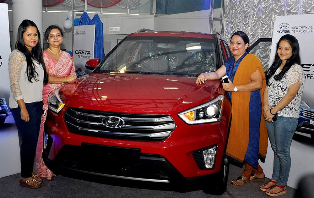 Women pose for photographs after the launch of new Hyundai vehicle Creta in Guwahati.