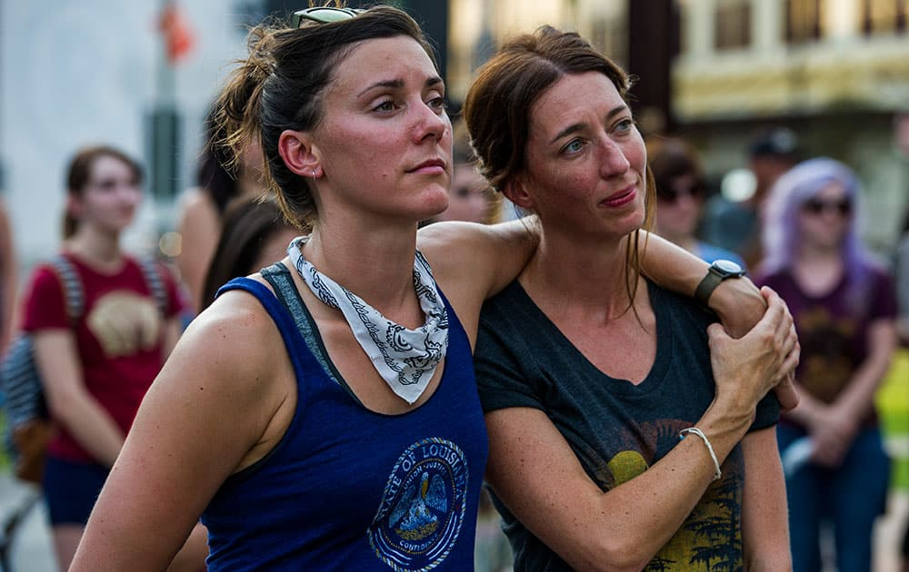 Marla Kristicevich and Paige Krause embrace each other as they listen during a vigil to remember and honor the victims of a deadly shooting at The Grand 16 theater.