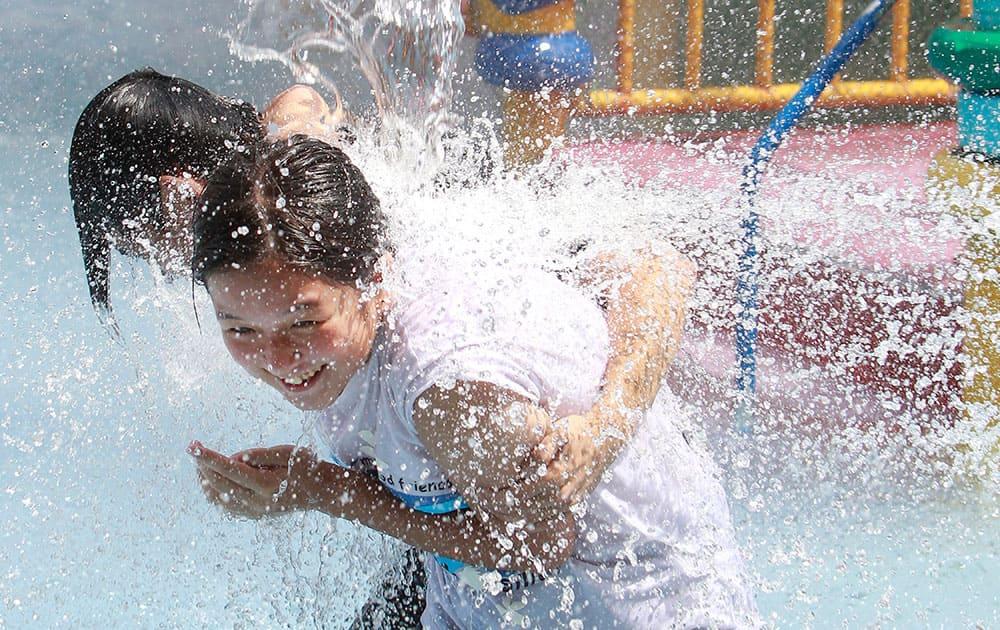 Two Taiwanese people enjoy the water at a pool in Taipei, Taiwan.