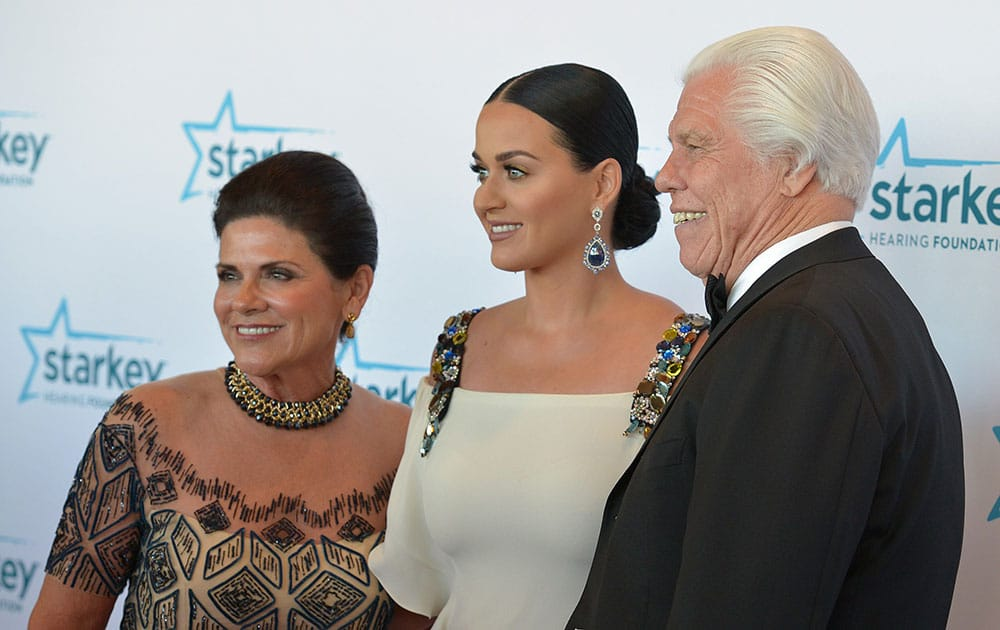 Katy Perry, center, poses with Starkey Hearing Foundation founders Tani Austin, left, and Bill Austin during the Starkey Foundation's annual gala in St. Paul, Minn.