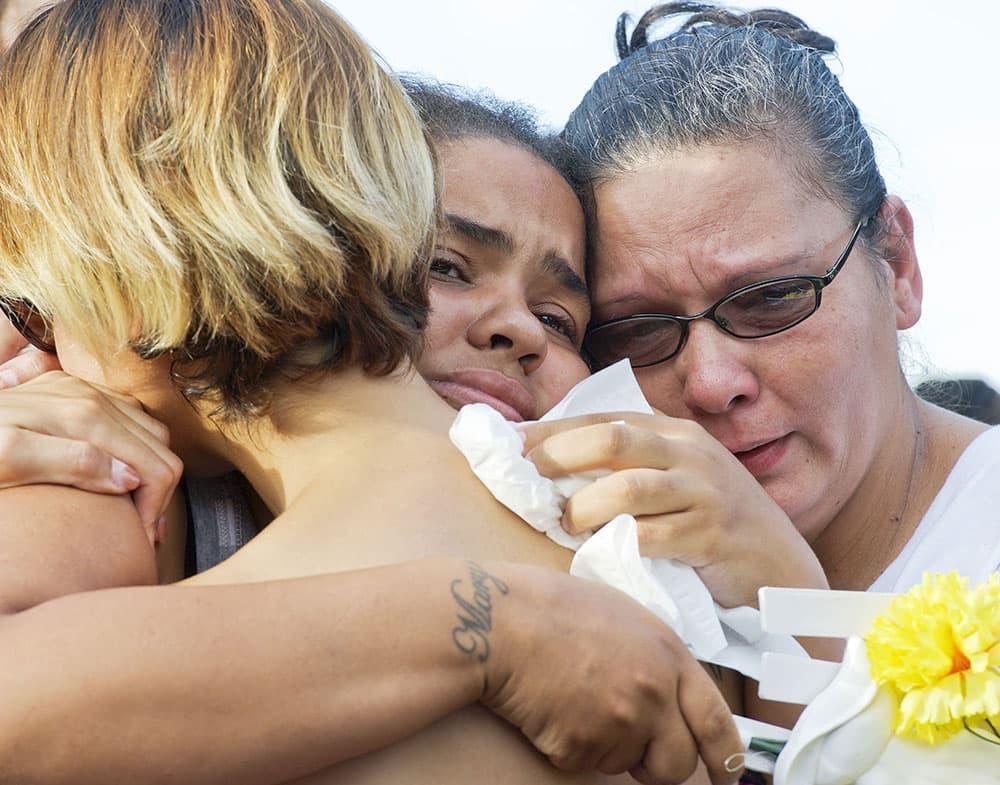 Mary Kirkland, center, the mother of shooting victim Shakur Franklin, hugs Vanessa Belen, left, the mother of shooting victim Elijah Jackson, during a memorial,  in Erie, Pa.