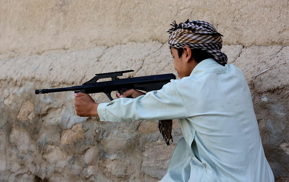 an Afghan boy plays with his friends using a toy gun, in Kabul, Afghanistan.