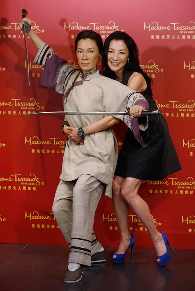 Malaysian martial arts actress Michelle Yeoh poses with her new wax figure at Madame Tussauds in Hong Kong.