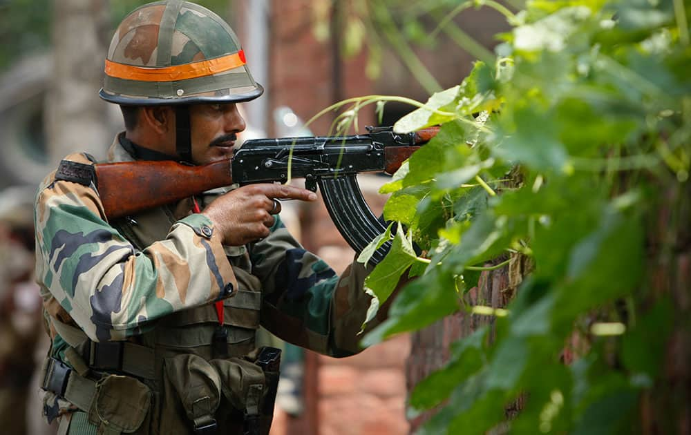 An Indian army soldier holds an AK-47 assault rifle during a fight in the town of Dinanagar, in the northern state of Punjab, India.