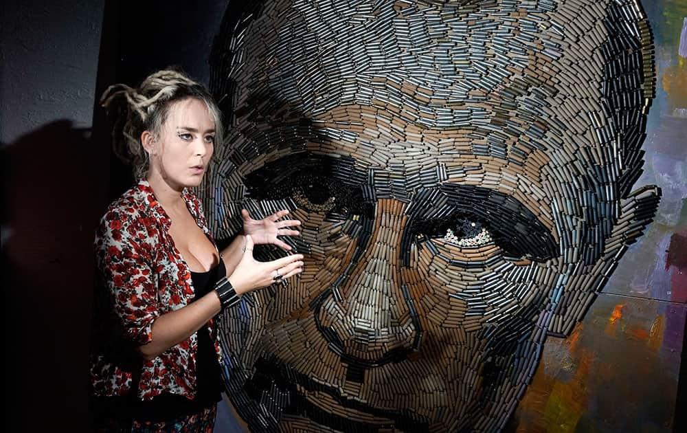 Ukrainian artist Dasha Marchenko poses next to her portrait of Russian President Vladimir Putin, made by out of cartridge cases, in the artist's studio in Kiev, Ukraine.