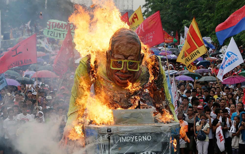 Protesters set on fire to the giant effigy of Philippine President Benigno Aquino III during a rally leading to the House of Representatives to coincide with Aquino's last State-of-the-Nation-Address or SONA at suburban Quezon city northeast of Manila, Philippines.